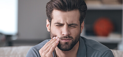 Young man holding the side of his mouth with dental pain