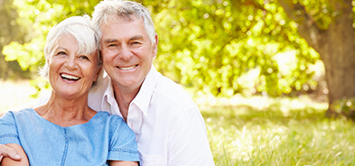 Older couple smiling outside to show off dental implants