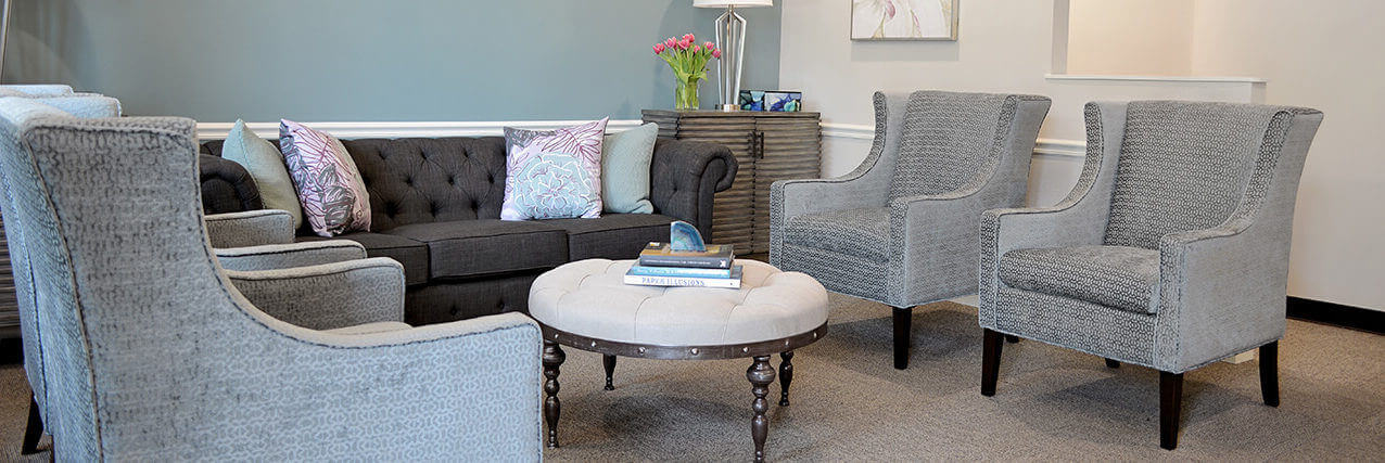Four Grey Chairs And Couch Along With Quilted Coffee Table In Waiting Room