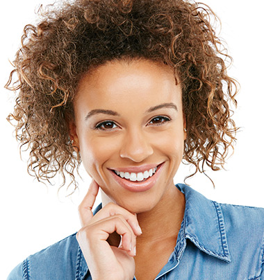 woman with curly brown hair and bright, white teeth smiling, hand rested on her chin