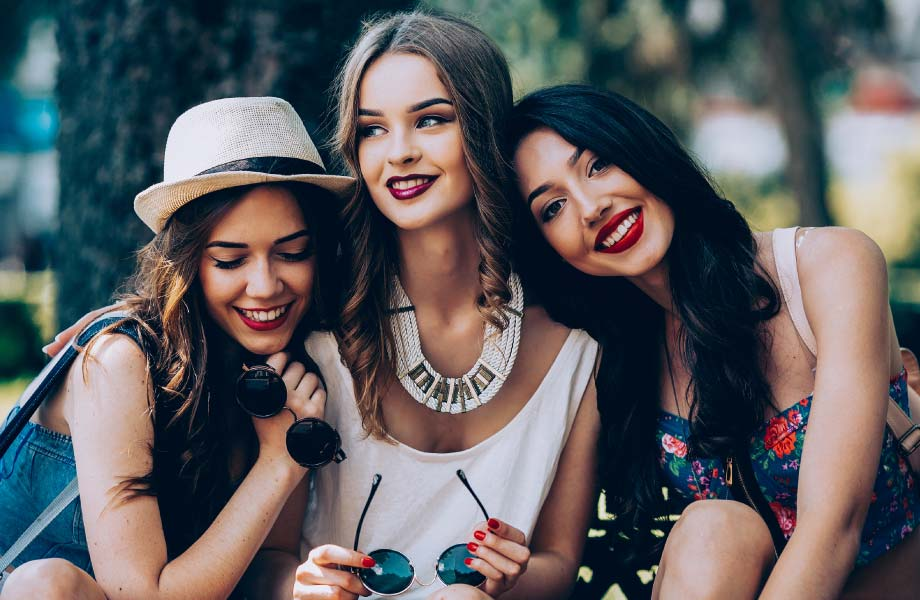 Three young brunette women holding sunglasses sitting outside wearing dark lipstick and showing off white teeth.
