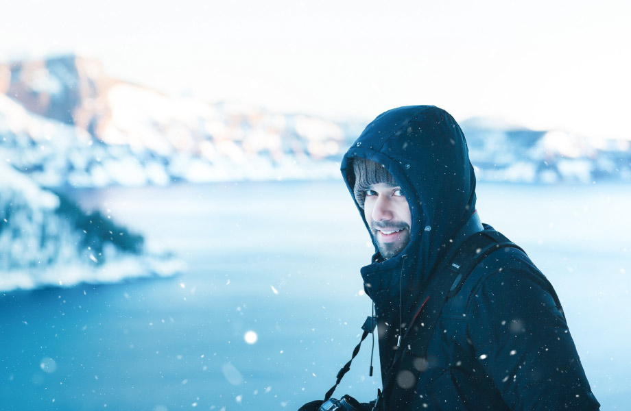 Man in black hooded coat standing in the snow in front of a lake and mountains