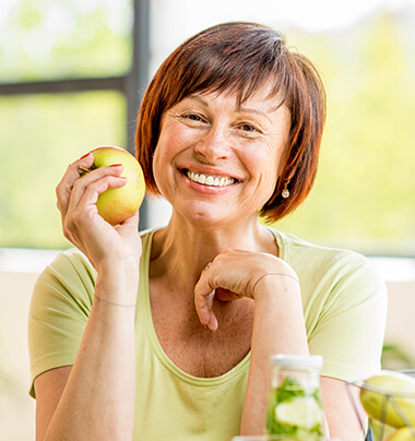 woman with dental crowns smiling as she holds an apple in her hand