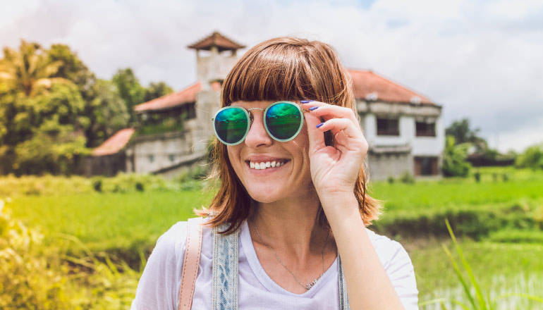 Smiling brunette woman wears blue and green sunglasses outside in a green field by an old building