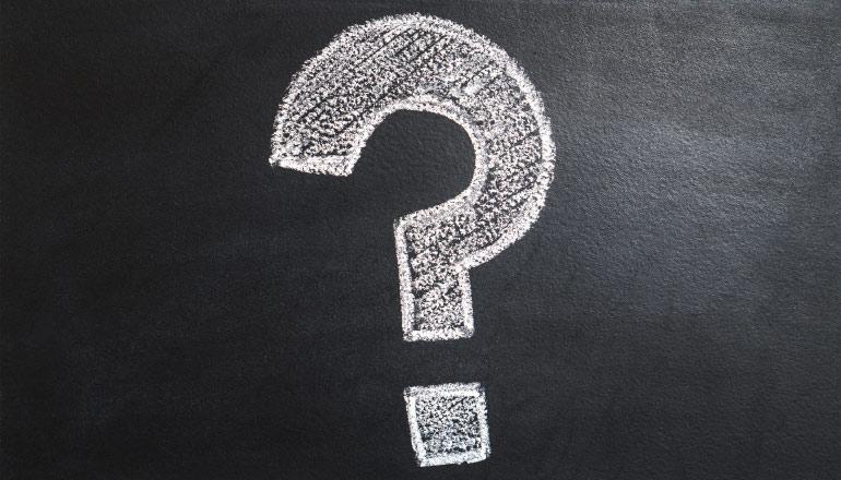 White question mark written in chalk on a black chalkboard background