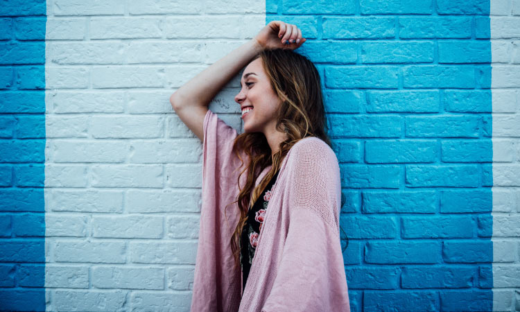 Brunette woman wearing a pink cardigan smiles as she leans against a brick wall painted 2 colors of blue