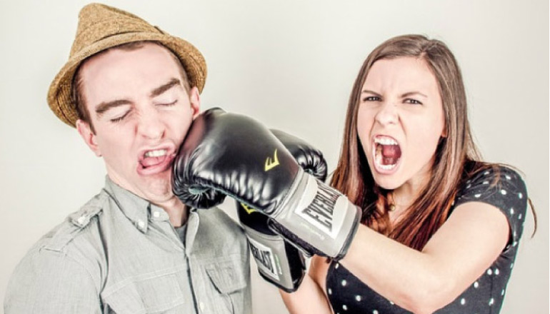 woman punching man in the jaw with boxing gloves creating a dental emergency