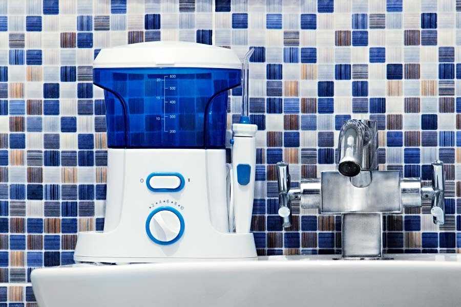 Water flosser on a sink in front of a blue mosaic tile backsplash