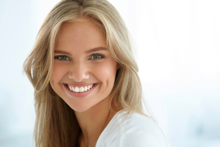 young woman smiles to show off her white smile